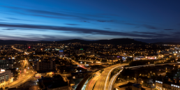 Night time cityscape of Belfast showing roads and motorways, street lights and mountains in the distance