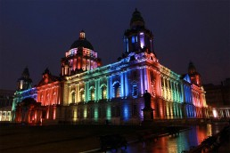 Night time and the exterior of Belfast City Hill is lit up with pillars of gree, blue, purple, red and yellow light.