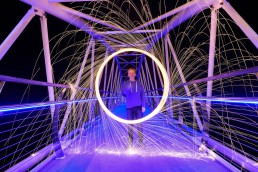 Boy playing with a sparkler type of firework on contemporary bridge, white and lilac glow
